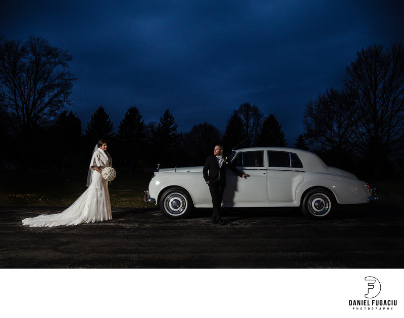 Bride and groom posing by Rolls Royce classic car