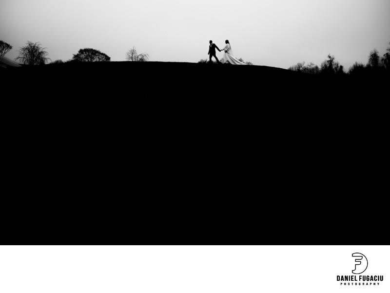Bride and groom walking on a hill