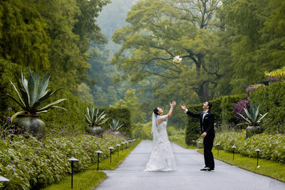 Bridal bouquet toss in the air | bride and groom