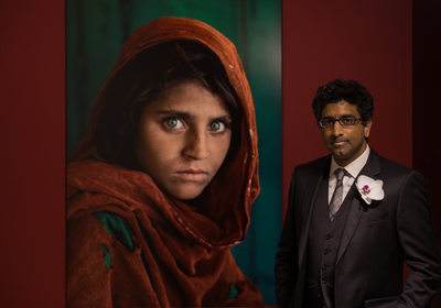 Grooms portrait next to famous portrait Afghan Girl