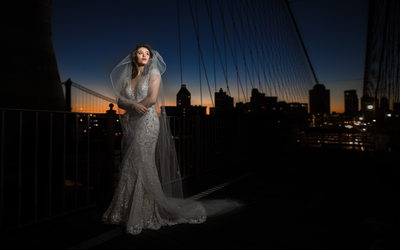 Brooklyn Bridge bride with veil in the wind at sunrise