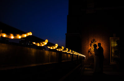 Silhouette of bride and groom at night on the rooftop