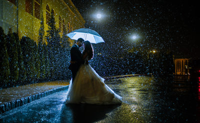 Portrait of Bride and Groom under umbrella in the rain