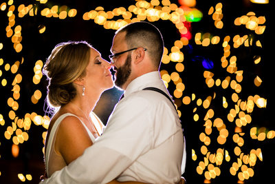Bride and groom snuggling surrounded by sparkly lights
