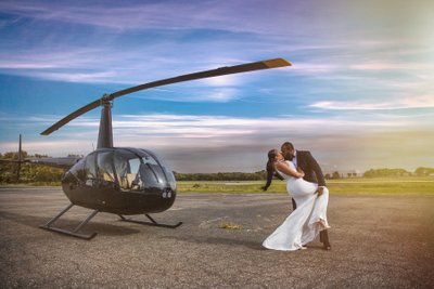 Wedding couple kissing by helicopter