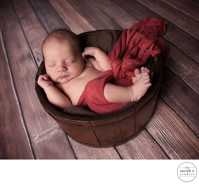 St. Louis Newborn Boy in Cardinal Red Wrap on Floor