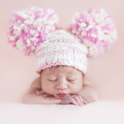 Newborn Girl in Fenton, MO Wearing a Pom Pom Hat