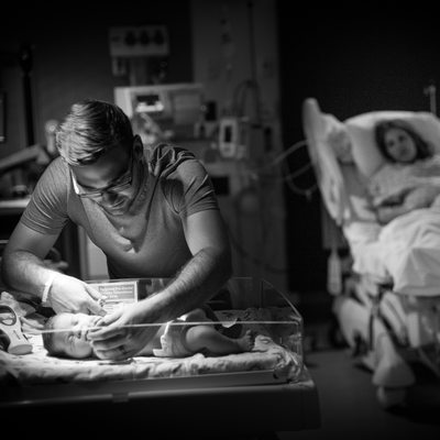 Darling View of Dad and Newborn Baby with Mom Watching