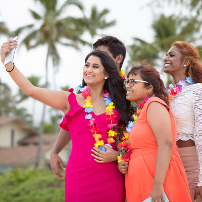 Wedding guests taking selfies on the beach