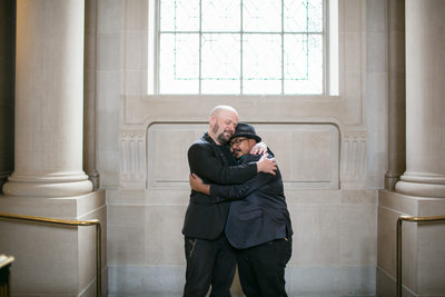 Grooms embrace after their San Francisco City Hall wedding