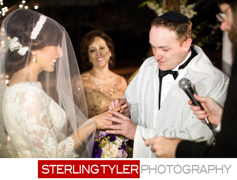 jewish groom puts ring on brides finger photograph