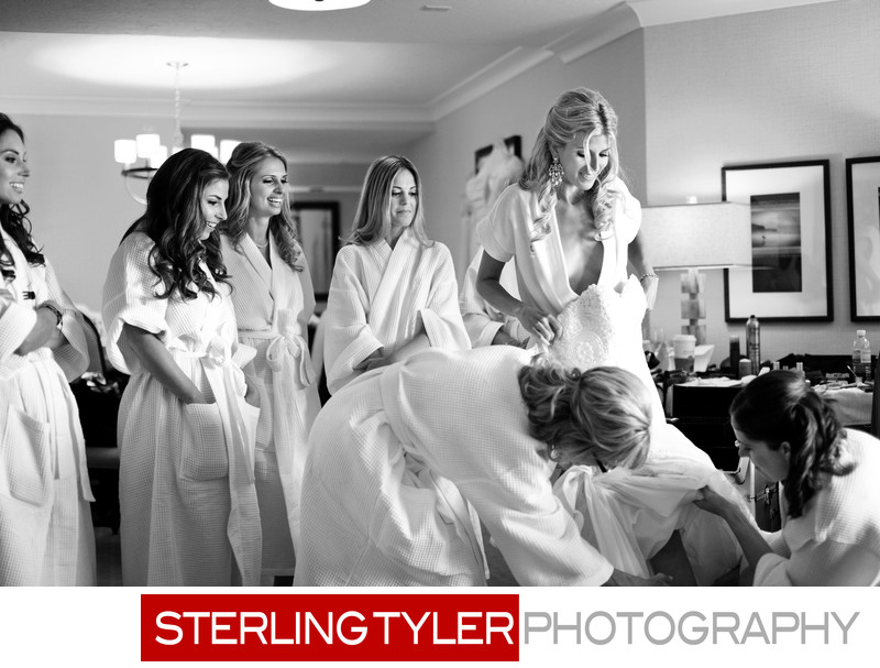 bride getting ready putting on dress with bridesmaids
