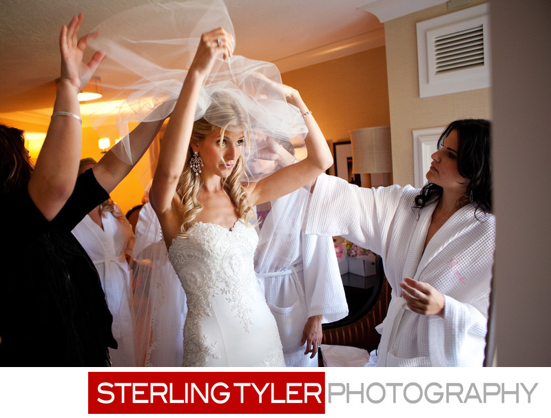 bride applying veil with bridesmaids