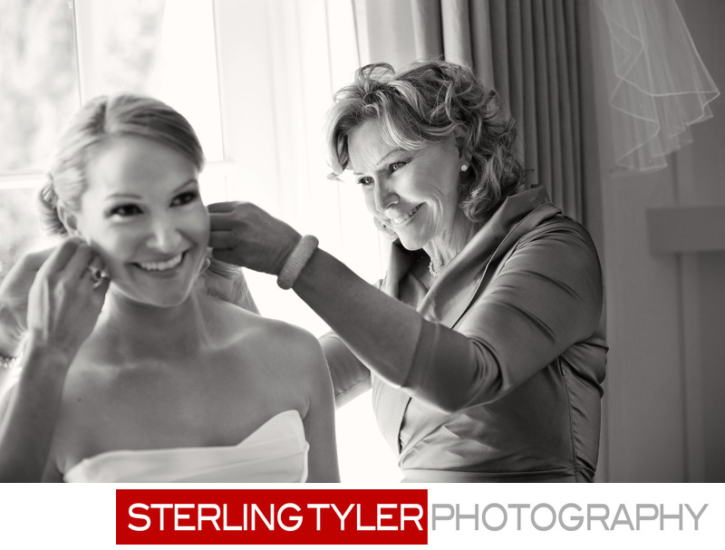 bride and mom put on earrings and jewelry candid photo