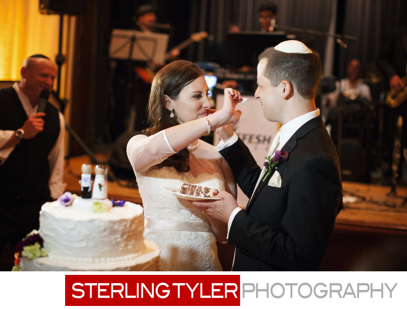 couple feeds each other cake at jewish wedding