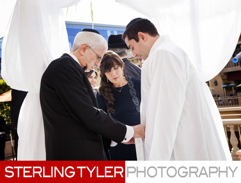 orthodox jewish groom puts on kittel during wedding