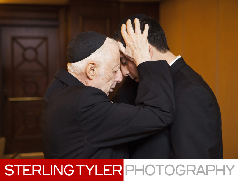 orthodox jewish groom receives blessing from grandfather