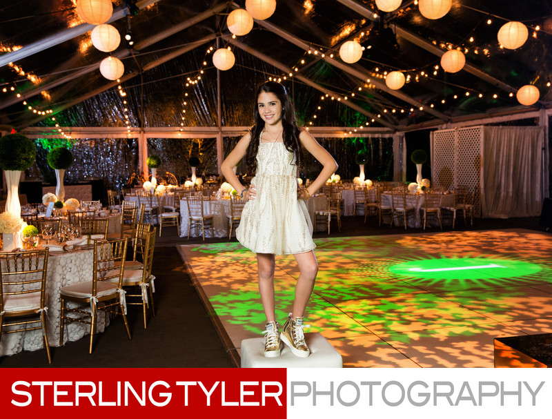 bat mitzvah girl poses with reception decor