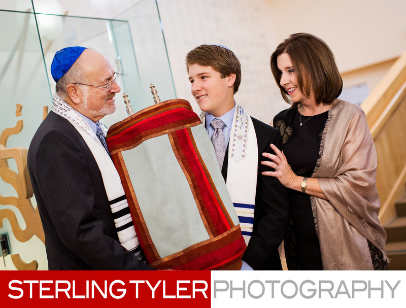 bar mitzvah boy with parents and torah at kehillat israel