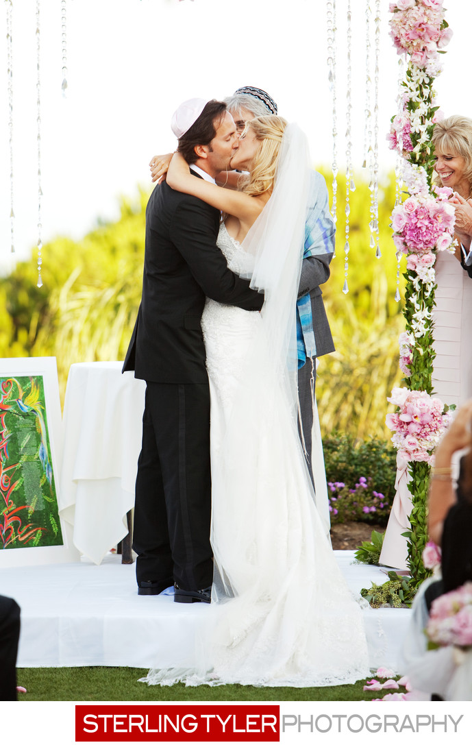 bride and groom kiss after jewish wedding ceremony