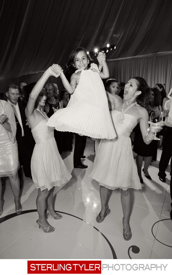 brides maids dancing with flower girl on white dance floor