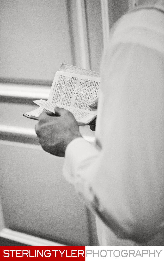 orthodox jewish groom praying before wedding prayerbook