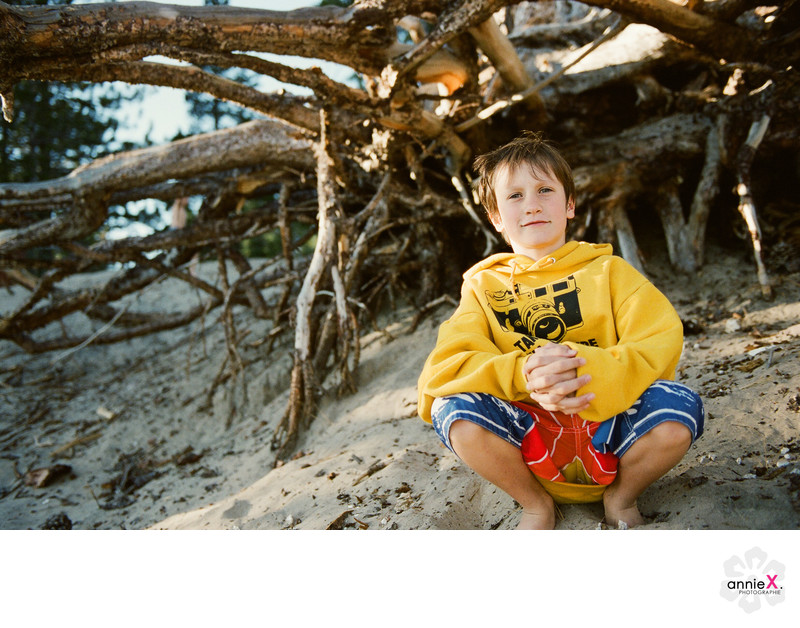 Boy in front of tree at lake Tahoe beach