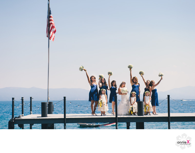 Playful bridesmaids on pier