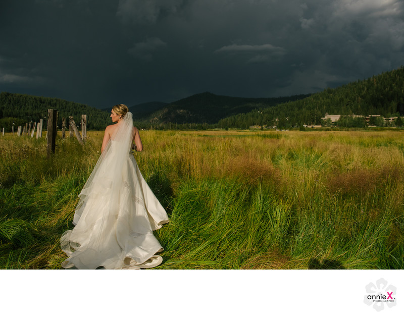 bride in Squaw Valley meadow with stormy skies
