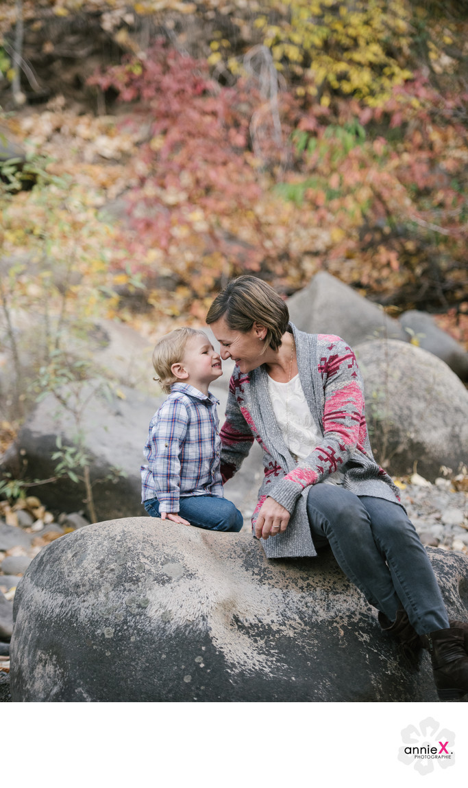 Mother and toddler son on rock in truckee river