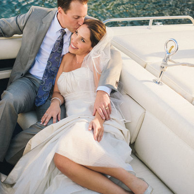 Bride and groom getting comfy in boat at West Shore