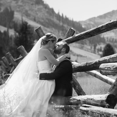 Newlyweds kissing leaning on wood fence in Squaw Valley