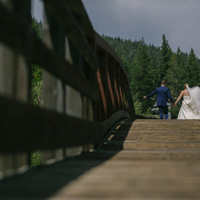Bride and groom walking on footbridge in Squaw valley