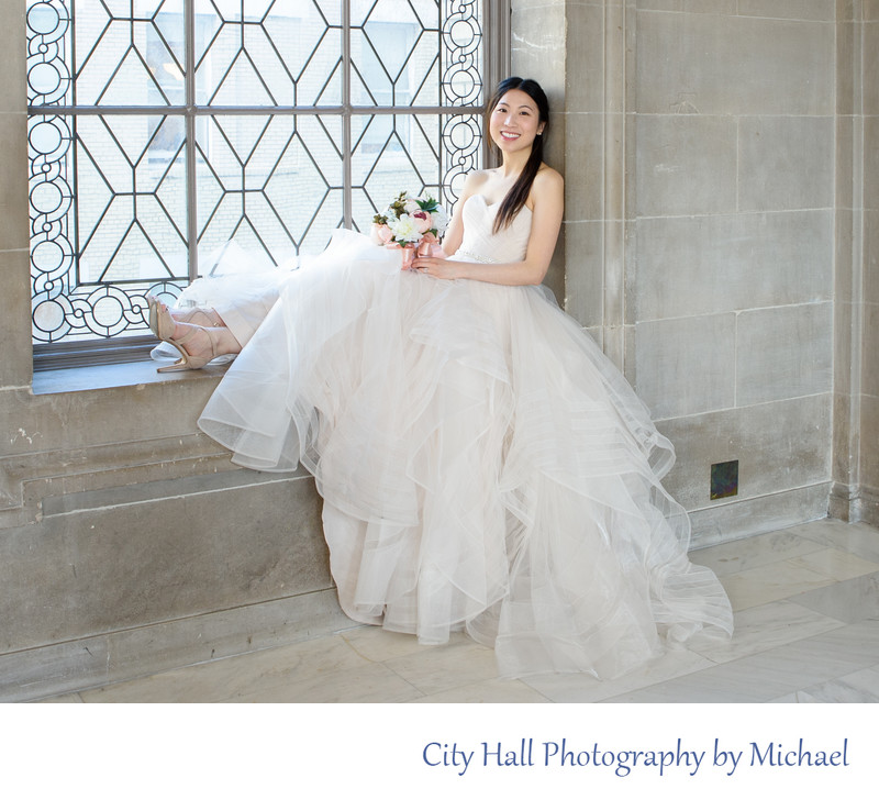 Beautiful Asian bride sitting in San Francisco city hall window