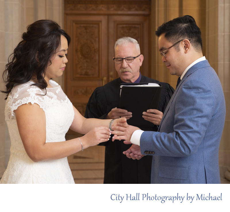 Bride placing ring on Groom during city hall marriage ceremony