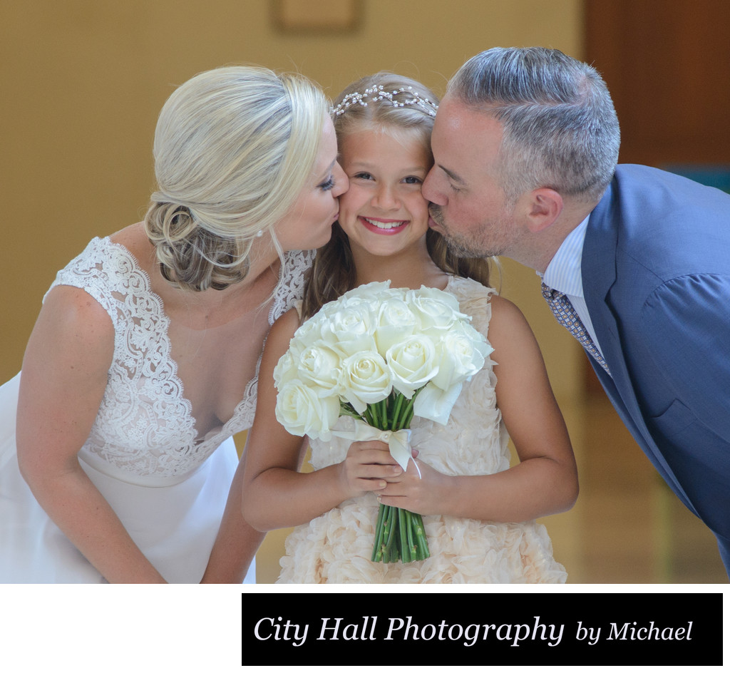 Bride and groom kissing  daughter at SF City Hall with Bouquet