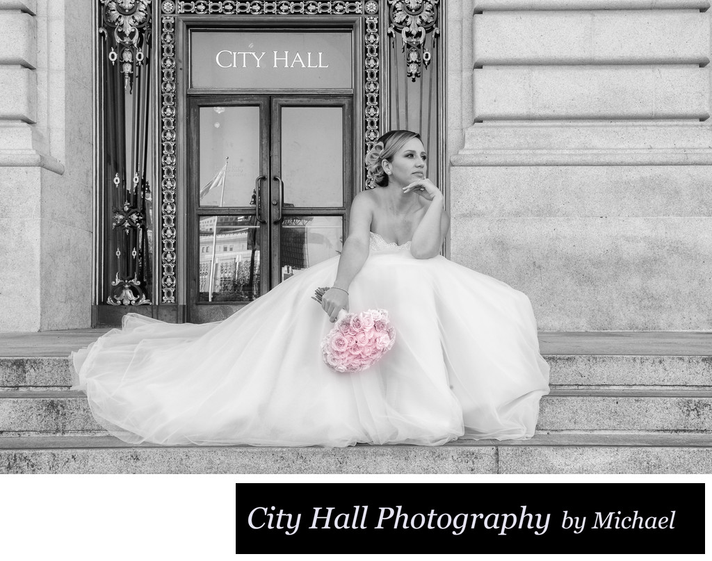 Bride sitting on the steps of San Francisco City Hall