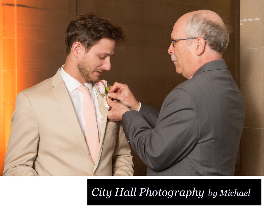 Dad and groom pinning on boutonniere flower  before ceremony