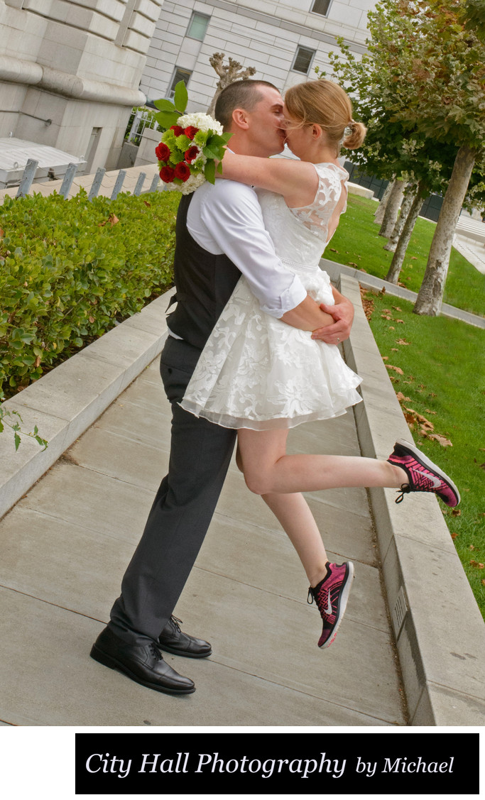 Lift kiss outside of San Francisco City Hall with red sneakers