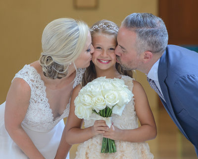 Bride and groom kiss daughter at SF City Hall