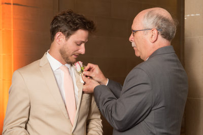 Dad and groom pinning on boutonniere flower