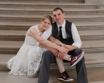Bride and groom on stairs with her red wedding sneakers