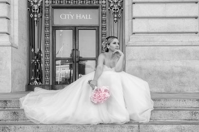 Bride on the Steps at San Francisco City Hall looking off in to the distance