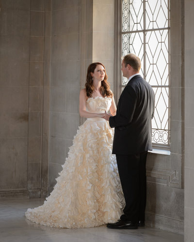 Bride and groom in natural light at a City Hall window