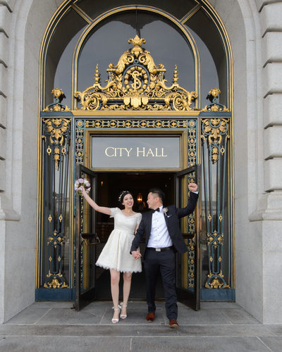 Newlyweds Walking out of San Francisco City Hall Celebrating
