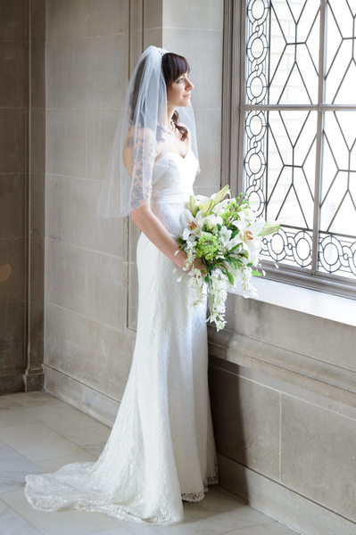 Bride looks out window at City Hall - Same Sex Wedding