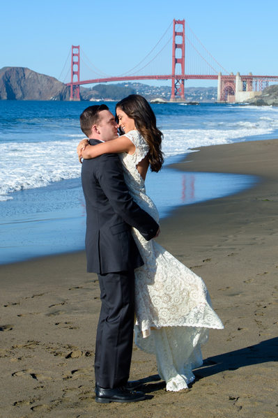 Groom Lifting Bride on Baker Beach with Golden Gate Bridge