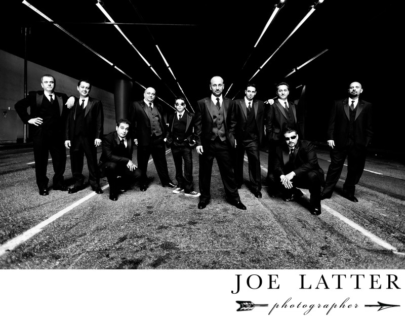 Creative black and white image of large wedding party and groomsmen in a gritty urban location.