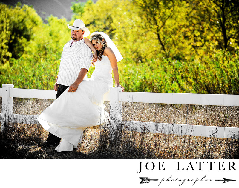 Country bride with groom wearing cowboy at together sitting on a fence.