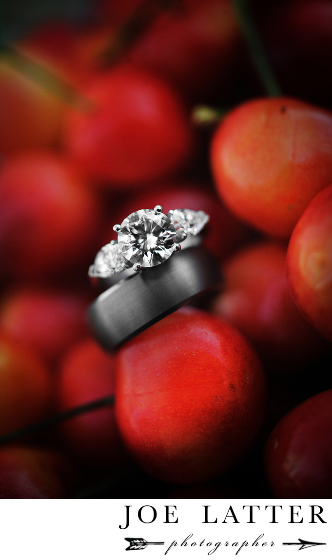 This is an image of a bride's wedding ring and a groom's wedding band photographed in a bowl of red cherries.